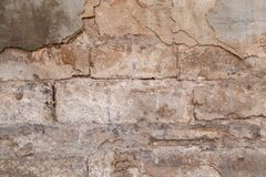 Gammal förstörd väggfasad med stupat cement och tegelstenar Texturbakgrundsflinga av murbruk från husväggen arkivfoton