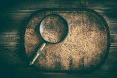 Gammal förstoringsglas eller loupe på korkbakgrund Royaltyfria Foton