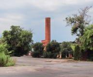 Gammal fabriksskorsten i renoverad grannskap Royaltyfri Fotografi