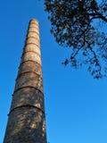 Gammal fabriksskorsten och blå himmel och träd royaltyfri foto