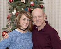 gammal fader 69-year och härlig 43 år gammal dotter som framme står av en julgran Royaltyfri Foto