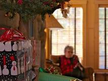 gammal farmor den höga damen tycker om mobiltelefonen, smartphone på jultid royaltyfria bilder