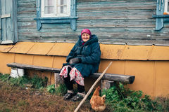 Gammal farmor nära hans hem i Ryssland Royaltyfri Fotografi