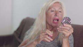 Gammal farmor som använder den lilla fackspegeln för att använda läppstiftmakeup Pensionerad blond kvinna som hemma gör makeup oc lager videofilmer