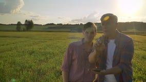 Gammal farsa som förklarar och visar nytt odla plan till hans son, bonde och arvinge som diskuterar projekt på vetefält lager videofilmer