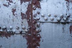 Gammal fastnitad rostig metallbakgrund arkivfoto