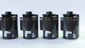 Gammal film för mm 35 i kassett på en vit bakgrund arkivfilmer