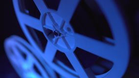 Gammal film för visning för 8mm filmprojektor på natten i mörkt rum med blått ljus Närbild av en rulle långsam rörelse Tappning stock video
