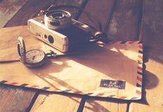 Gammal filmkamera, antika klockor och flygpostbokstav på den wood tabellen, Royaltyfri Fotografi