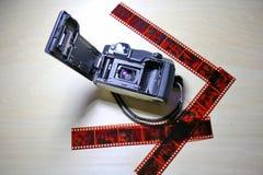 Gammal filmkamera med den använda filmen Arkivfoton