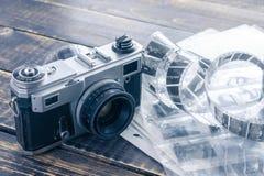 Gammal filmkamera, svartvit negativ film och stickor arkivfoto