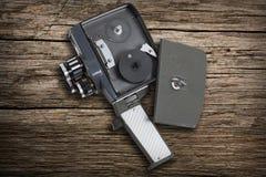 Gammal filmkamera toppna åtta på en skogsbevuxen bänk Arkivfoton