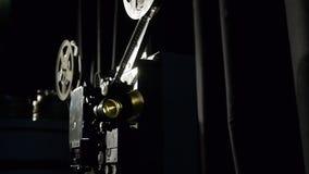 Gammal filmprojektor som spelar i natten Närbild av en rulle med en film lager videofilmer