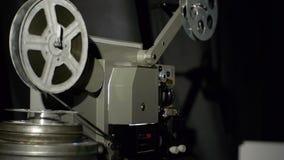 Gammal filmprojektor som spelar i natten Närbild av en rulle med en film Filmen har kört ut ur filmen arkivfilmer