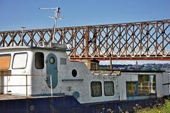 Gammal fiskebåt och bro bakom fotografering för bildbyråer