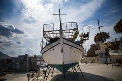 Gammal fiskebåt på kusten Ett skepp drog ashore Hamn i byn av Hersonissos på ön av Kreta, Grekland royaltyfria foton