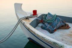 Gammal fiskebåt som anslutas på gryning Litet träfartyg på vattentidvattnet med rep Soluppgång i hamnen och havet Arkivfoton