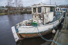 Gammal fiskebåt som förtöjas på flodpir royaltyfri fotografi