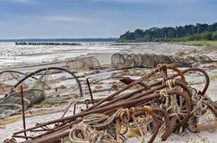 Gammal fiskeutrustning och bruten pir på den baltiska stranden Royaltyfri Bild