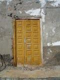 Gammal flagnande brun dörr i den vita väggen i Fuerteventura kanariefågelöar Arkivfoto