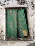 Gammal flagnande bruten grön dörr i den vita väggen i Fuerteventura kanariefågelöar Fotografering för Bildbyråer