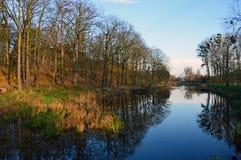 Gammal flod i de reflekterande träden för parkera under sista soliga dagar av nedgången arkivbilder