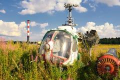Gammal flygplanflygkropp och rostiga helikoptrar på grönt gräs Royaltyfri Fotografi