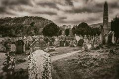 Gammal forntida keltisk kyrkogård och högt torn för gravstenar på berget och stormig himmelbakgrund i sepiastil arkivfoton