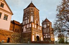 Gammal forntida medeltida slott med spiers och torn, väggar av stenen och tegelsten som omges av en skyddande vallgrav med vatten royaltyfri foto