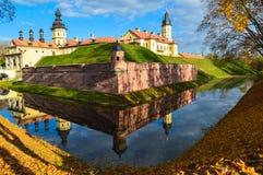 Gammal forntida medeltida slott med spiers och torn, väggar av stenen och tegelsten som omges av en skyddande vallgrav med vatten arkivfoto
