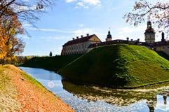 Gammal forntida medeltida slott med spiers och torn, väggar av stenen och tegelsten som omges av en skyddande vallgrav med vatten royaltyfri bild