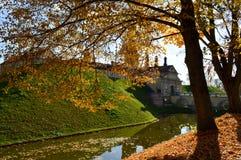 Gammal forntida medeltida slott med spiers och torn, väggar av stenen och tegelsten som omges av en skyddande vallgrav med vatten arkivfoton