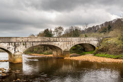 Gammal forntida stenbro över den lugna floden, härligt irländskt landskap scenisk sikt Royaltyfri Fotografi