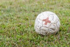 Gammal fotboll med lappat med suddig bakgrund Royaltyfri Foto