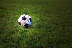 Gammal fotboll på gräs Arkivfoton
