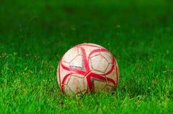 Gammal fotboll på gräsfält arkivbilder