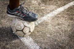 Gammal fotboll på konkret fält Arkivbild