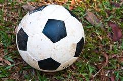 Gammal fotbollboll på grönt gräs Arkivbilder