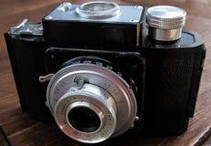 Gammal fotokamera på träbakgrund Retro stilaffisch för tappning Royaltyfri Foto