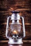 Gammal gaslyktabränning på tabellen och träplankabakgrund arkivfoto