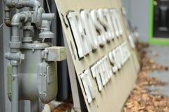 Gammal gasmeter bredvid ett övergett crossfittecken arkivfoto