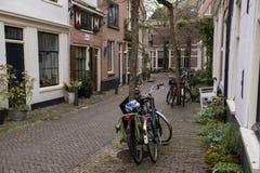 Gammal gata med parkerade cyklar Arkivfoto