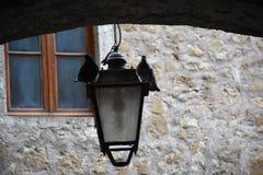 Gammal gatalampa med en vit duva och en svart duva Arkivfoto