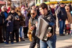 Gammal gatamusiker som spelar saxofonen Arkivbild