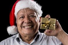 Gammal gentleman med Red Hat som erbjuder den guld- gåvan Royaltyfria Foton