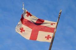 Gammal georgian nationsflagga med Röda korset och blå himmel Fotografering för Bildbyråer