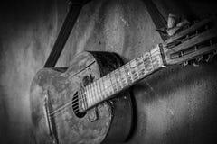 Gammal gitarr p? betongv?ggbakgrund med den suddiga framdelen och tillbaka bakgrund med bokeheffekt arkivfoton