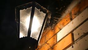 Gammal glödande lykta i en rengöringsduk, hängningar på hörnet av huset på natten eller i aftonen Futuristiskt mystiskt Moln av lager videofilmer