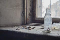 Gammal glasflaska med cigaretter på det gamla fönstret Arkivfoto
