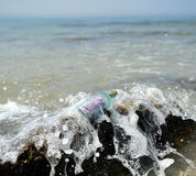 Gammal glasflaska med sedeln för euro 500 inom, kust av stranden Royaltyfri Bild
